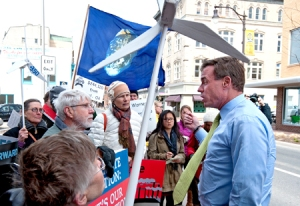 Sen. Mark Warner, D-Va., discusses environmental matters with protesters along Harrisonburg's Main Street on Wednesday. The protest focused on the Keystone XL pipeline, but the 70 or so people who rallied during Warner's visit to the Friendly City regarded it as just the centerpiece for broader environmental concerns. (Photos by Jason Lenhart / DN-R)