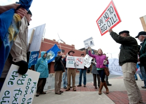 Environmental protesters prepare to march along Main Street as they make their statement about Sen. Mark Warner's support of the Keystone XL pipeline project. Warner, D-Va., was in Harrisonburg for an entrepreneurs' roundtable.